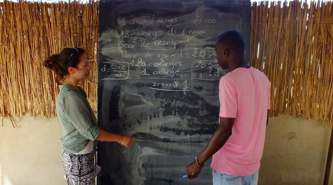 A Teaching volunteer in Senegal helps a local boy during a lesson.